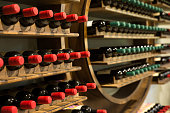 Selective focus of wine rack on wall in wood material full, to store red and white wine bottle in a row in cellar, cool and in good conditions.Some of those are old wine bottle with dust