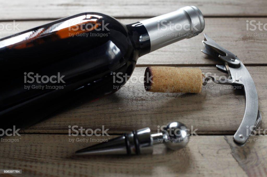 wine bottle, bottle cap, cork and corkscrew on wood table