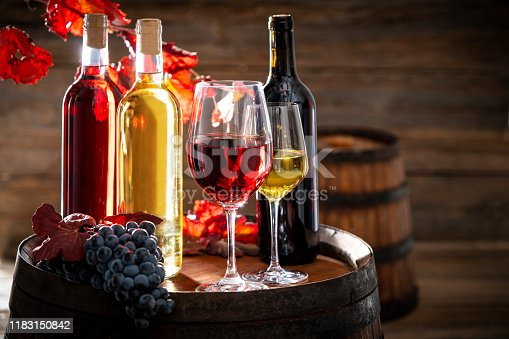 wine bottle and glass on wine oak barrel still on wooden background with red autumn grape leaves and cluster