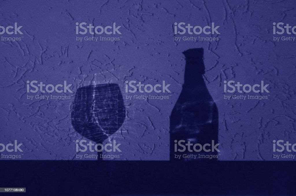 Wine bottle and glass shadow in blue tone. stock photo