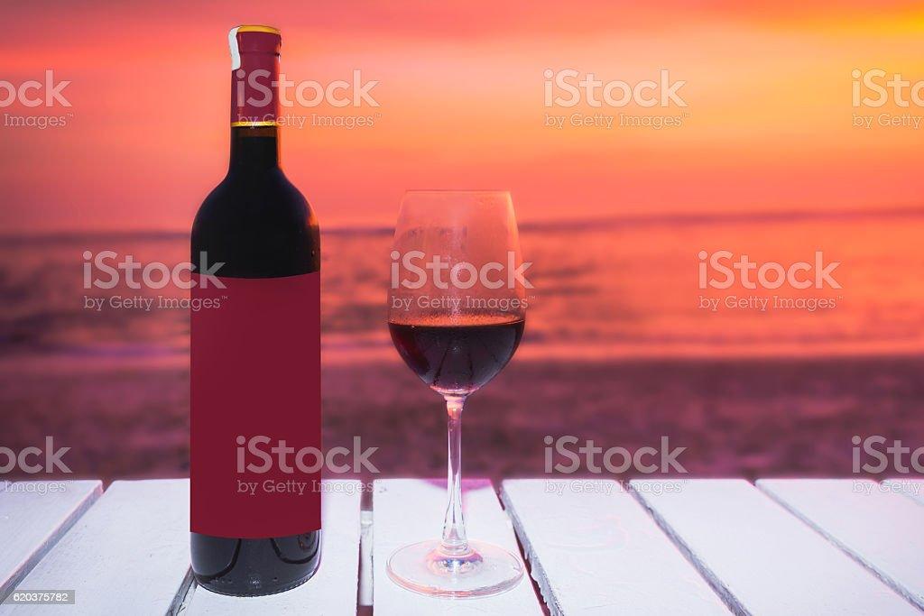 Wine bottle and glass with sunset backgrounds zbiór zdjęć royalty-free
