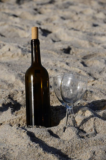 Wine bottle and glasses on the Beach stock photo