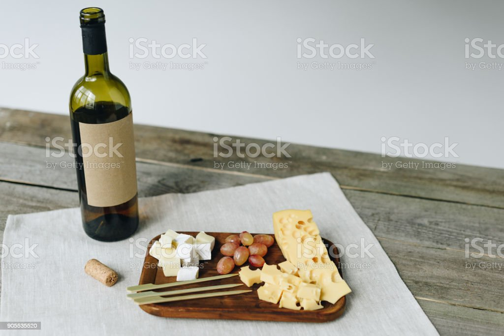 Wine bottle and plate with cheese and grapes stock photo