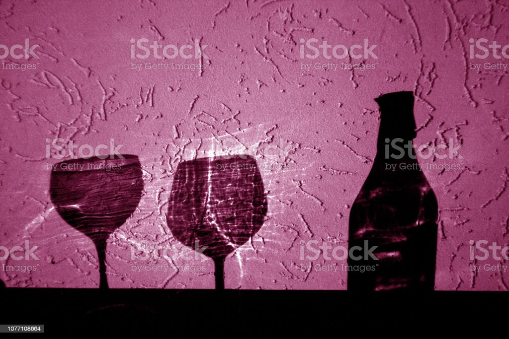wine bottle and two glasses shadow in pink. stock photo