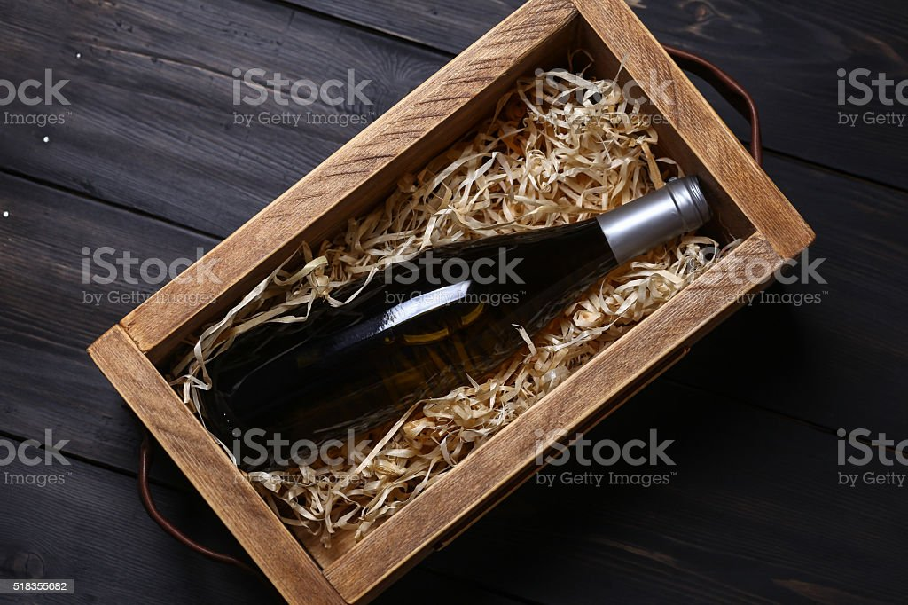 Wine bottle in a crate Bottle of white wine in a wooden crate with wood shavings on a dark wooden surface Alcohol - Drink Stock Photo