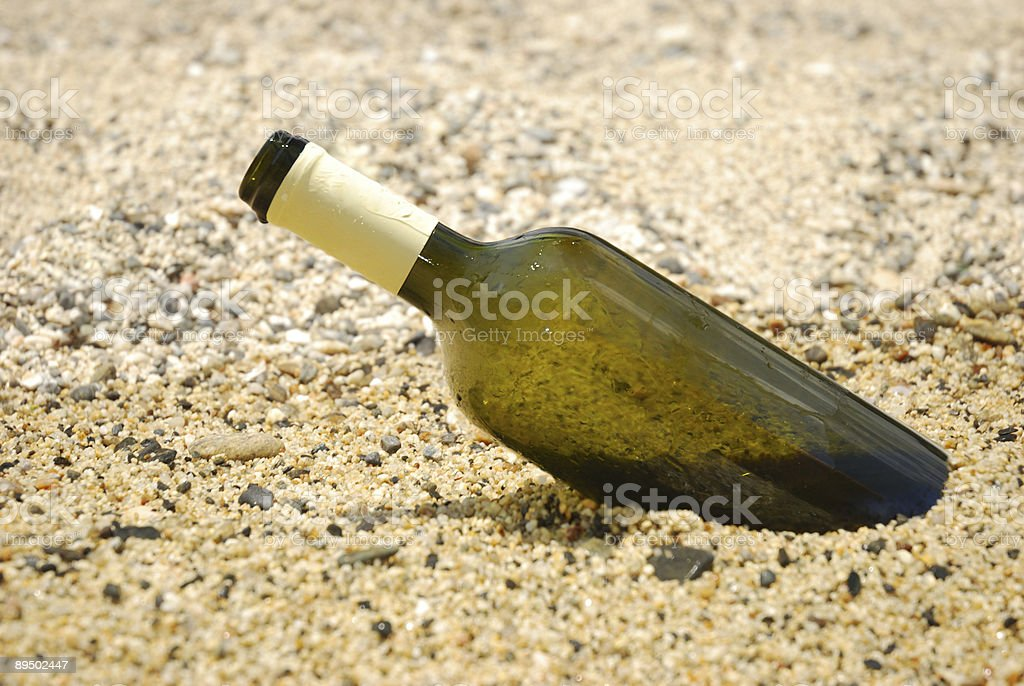 Wine bottle in the sand royaltyfri bildbanksbilder