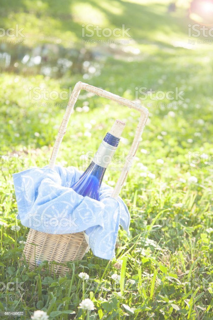 Wine bottle in wicker basket in meadow ready for summer picnic. royalty-free stock photo