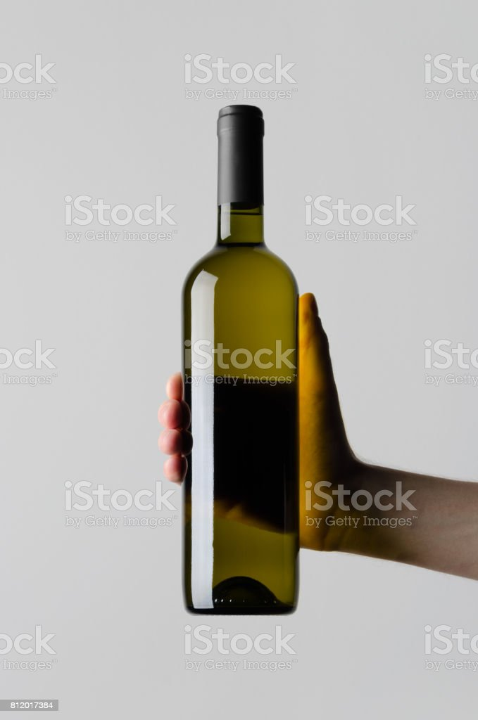 Wine Bottle Mock-Up - Male hands holding a wine bottle on a gray background stock photo