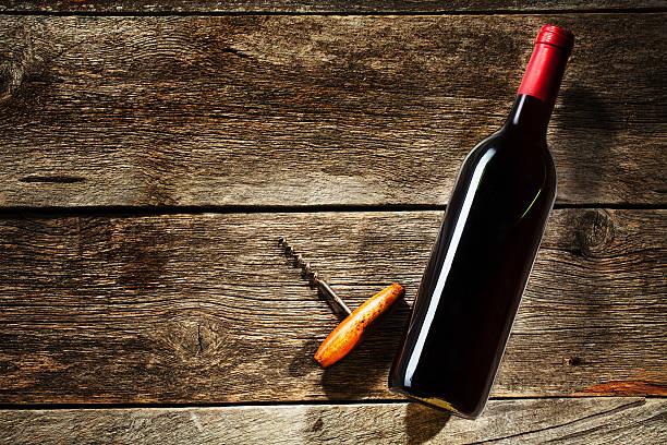 Wein und eine Flasche auf einem hölzernen Hintergrund – Foto
