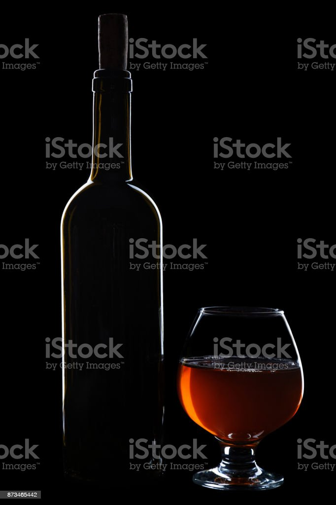 Wine bottle with a cork and wineglass with a beverage on a black background stock photo