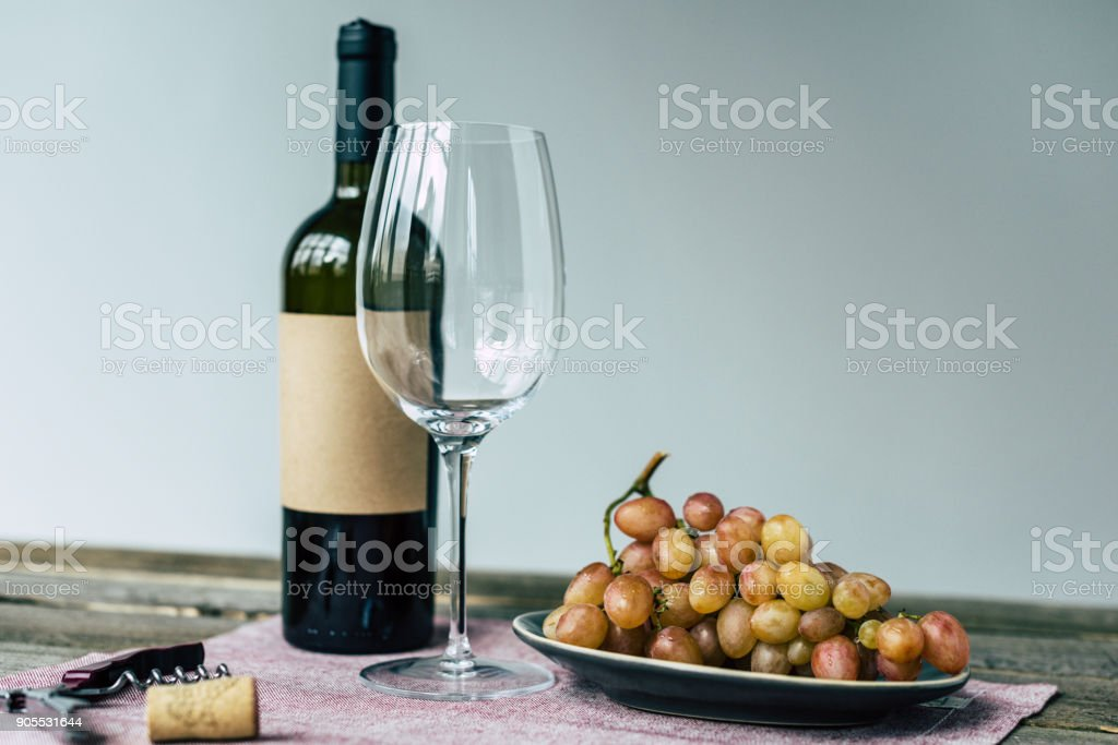 Wine bottle with empty glass and grapes stock photo
