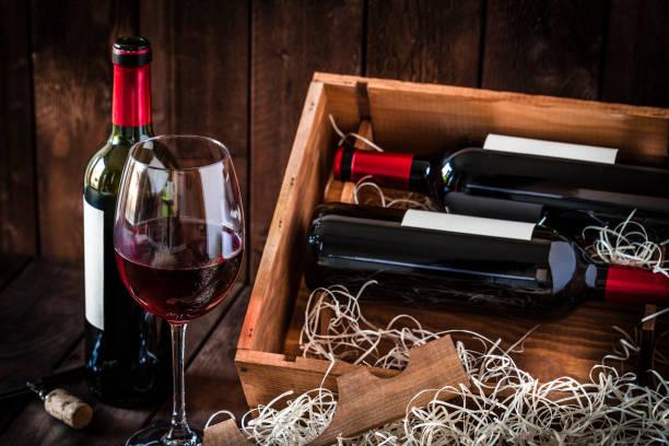 vinflaskor och vinglas sköt rustika träbord - wine box bildbanksfoton och bilder