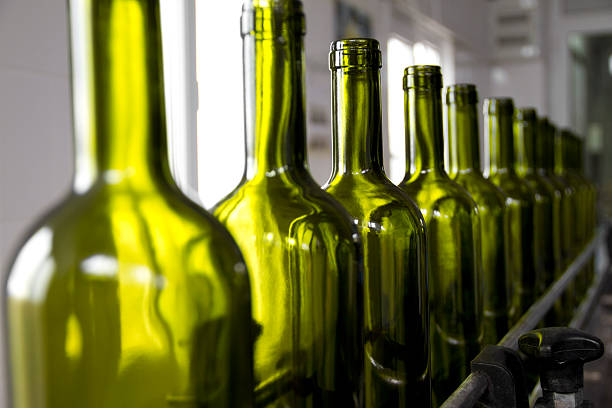 wine bottles colored green on an assembly line - bottling plant stock photos and pictures
