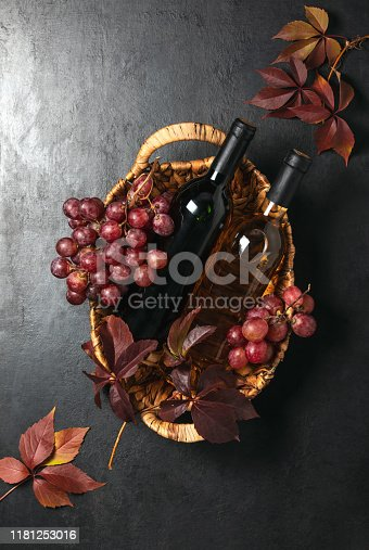 istock Wine bottles in a rustic basket, top down view 1181253016