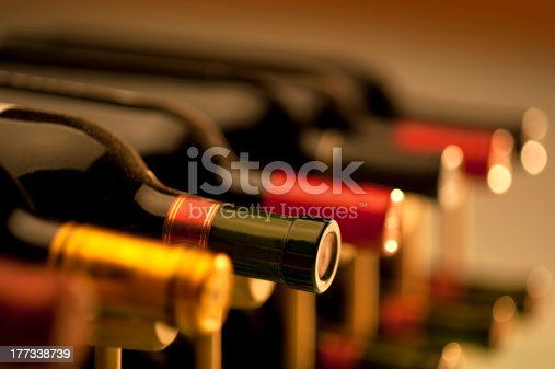Red and white wine bottles in a rack with very limited depth of field