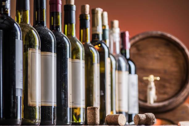 Wine bottles in row and oak wine keg. stock photo