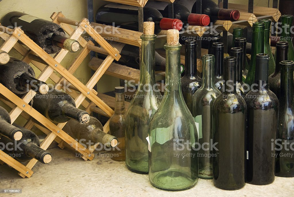 Wine bottles, old and new stacked among clutter royalty-free stock photo