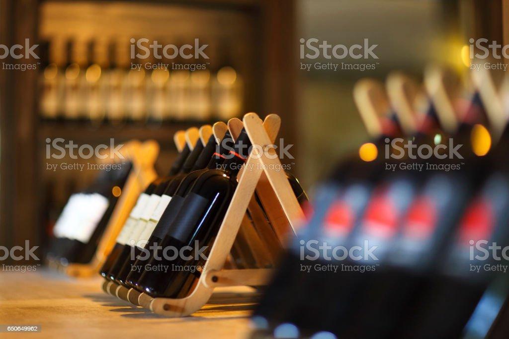 Wine bottles on a wooden shelf. stock photo