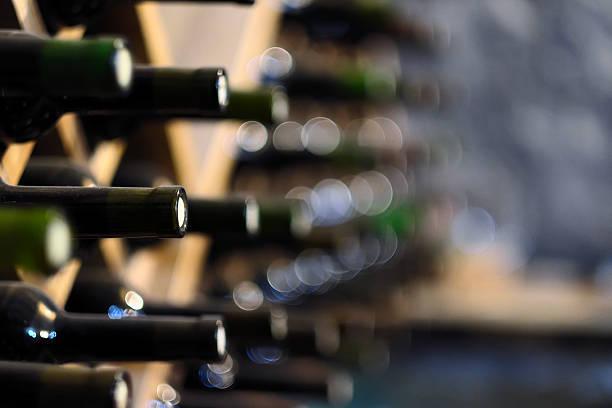 Botellas de vino en bastidores de apilado de madera - foto de stock