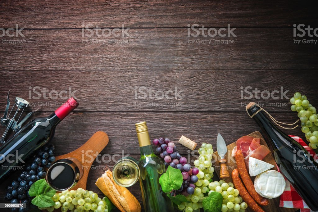Wine bottles with grapes, cheese, ham and corks stock photo