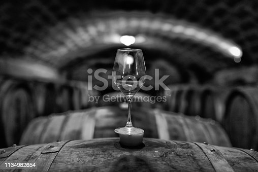Glass standing on barrel in wine cellar. Black & white photo.
