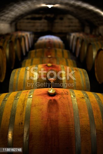Glass standing on barrel in ancient wine cellar.