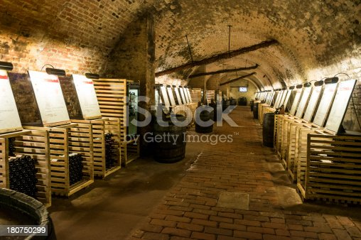 Wine cellar and wine store interior with thousands of bottles of wine and barrels.