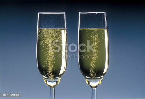 flute of sparkling champagne on grey gradient background