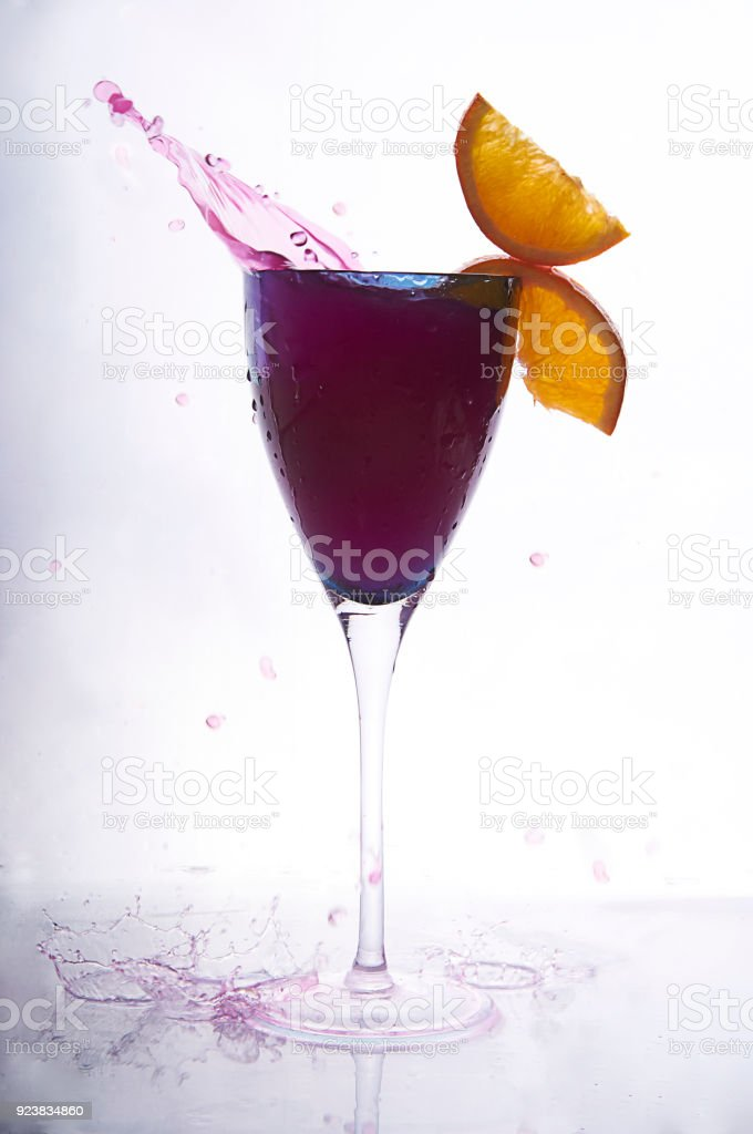 wine cocktail in blue glass decorated with oranges. splashing red...