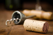 A wine cork with a corkscrew, stem of a wine glass and wine bottle in the background.  Cork is blank and could be used for text.