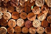A large group of used wine cork stopper with various vintage years showing forming the background with a rustic wood surface in the foreground. Background design for the wine industry, wine tasting events, and restaurants and bars businesses. Photographed with copy space. Studio still life close-up photography in horizontal format.