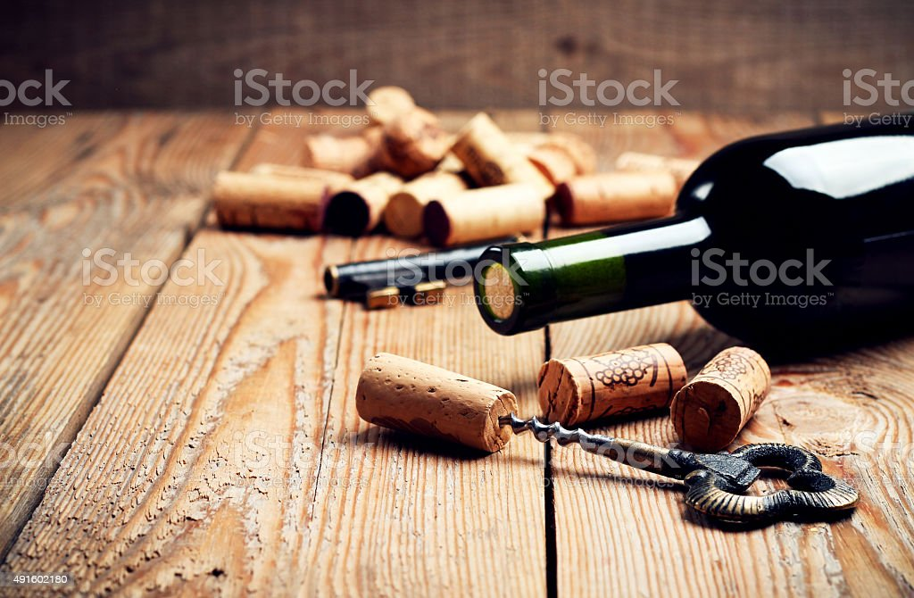 Wine corks, bottle and corkscrew on a wooden table royalty-free stock photo