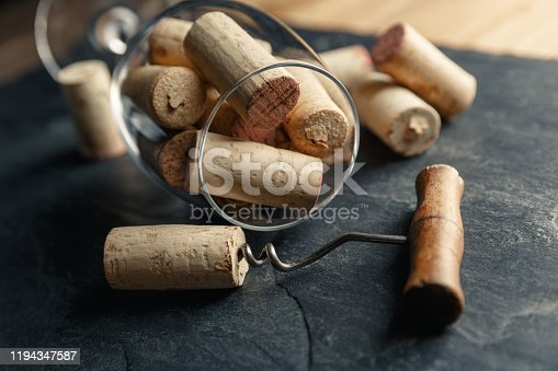 Wine corkscrew with a cork and wine glass full of corks on a black rocky slate background