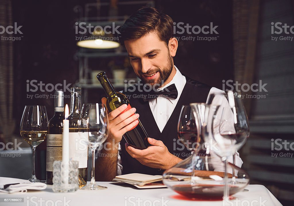 Wine critic holding bottle of scarlet drink with smile stock photo