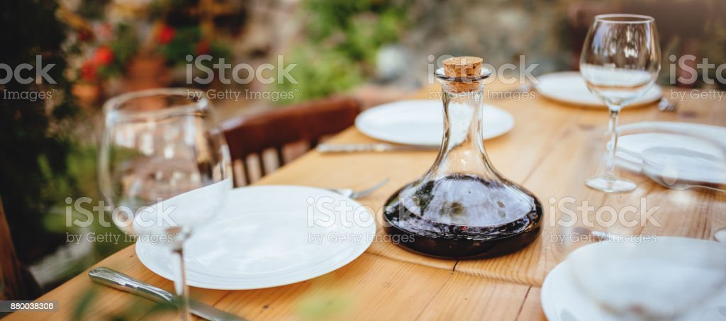 Wine decanter and glasses on dining table stock photo