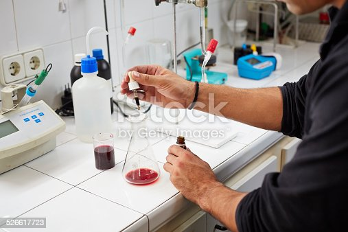 Oenologists checks the finished wine acidity at the laboratory