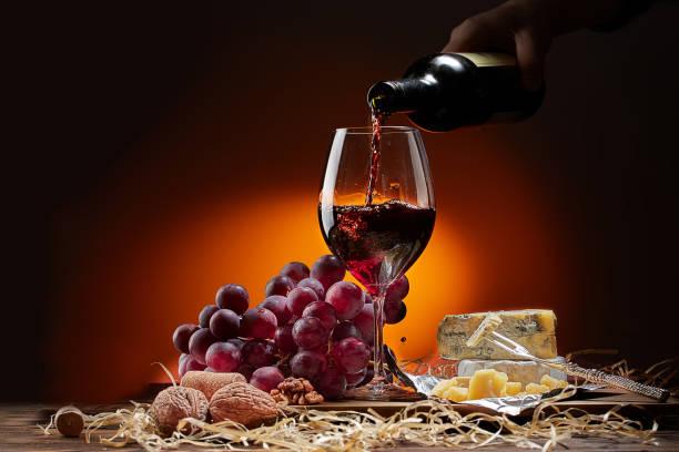 Vino fluye de la botella en el vidrio. En la tabla son diferentes variedades de queso y uvas. Fondo oscuro. - foto de stock