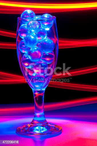 istock Wine Glass and Clear Marbles Blue and Red Light Painting 472206416