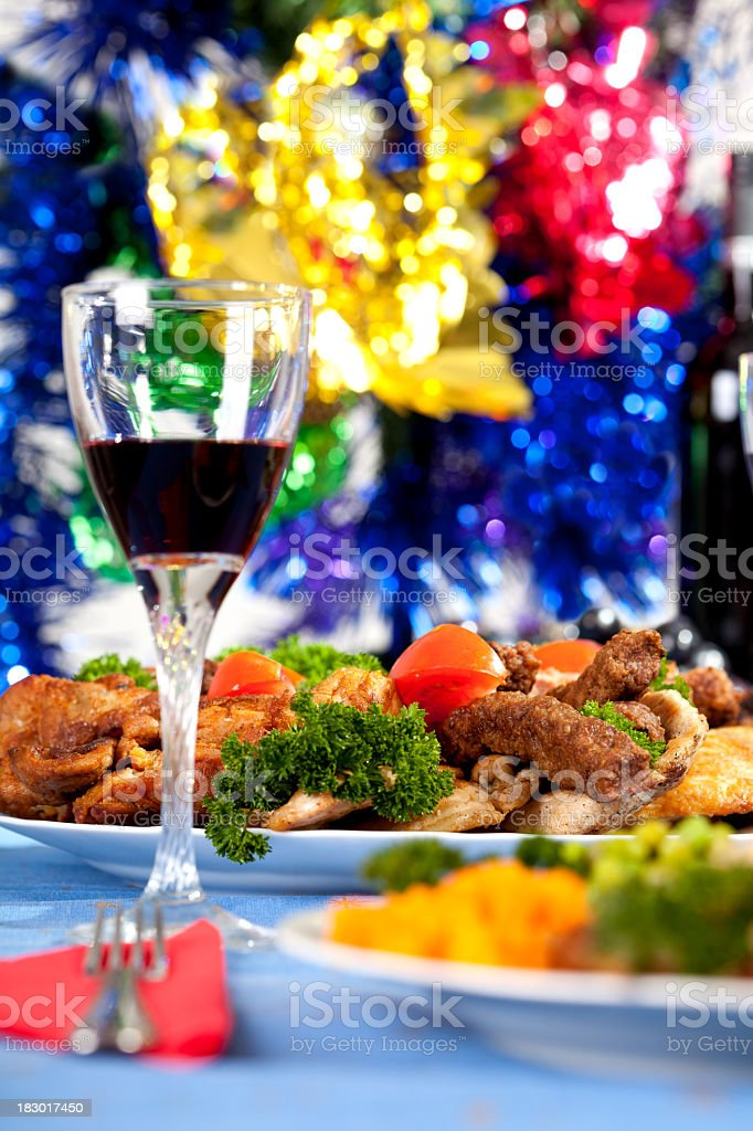Wine glass and food on the table with Christmas decoration royalty-free stock photo