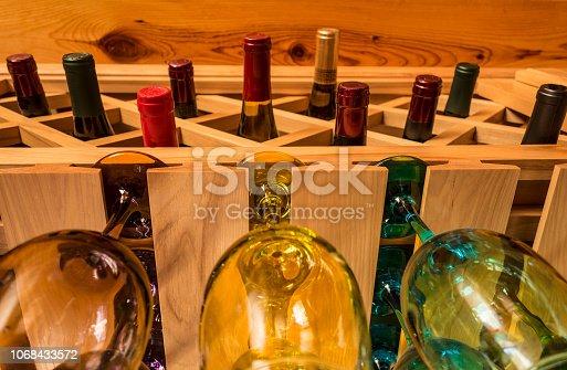 Full wine bottles over hanging wine glasses. Sonoma, California.