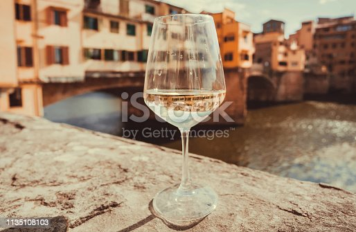 Wine glass and view on bridge Ponte Vecchio in historical Florence, Tuscany. River and ancient cityscape in Italy.