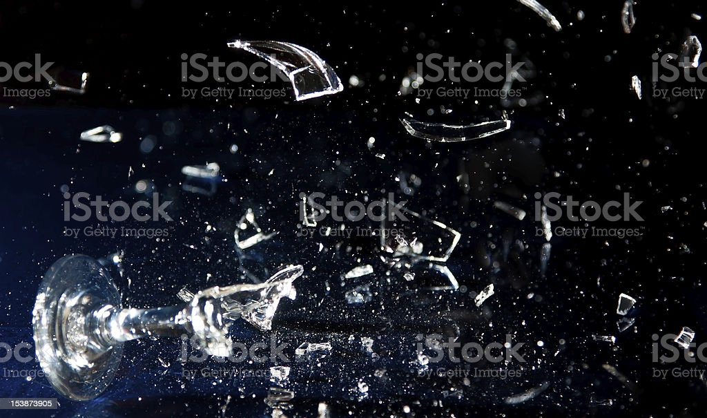 Wine glass breaking into pieces stock photo