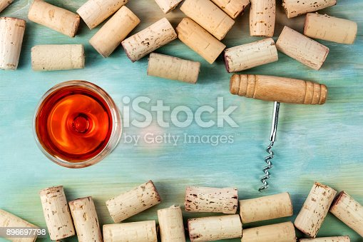 istock Wine glass, corkscrew, and corks on teal background with copy space 896697798