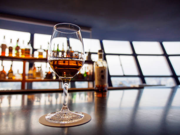 Wine glass filled with whisky at a sky bar stock photo
