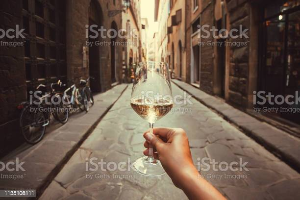 Wine glass in hand of happy tourist walking past historical houses of picture id1135108111?b=1&k=6&m=1135108111&s=612x612&h=h4gkdwa43s2jhphehsqv1h0v1i66qbarovbw2 lmlqc=