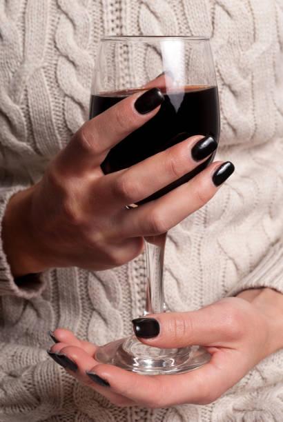 weinglas in junge weibliche hände mit schwarzen nägeln und pullover - herbst nagellack stock-fotos und bilder