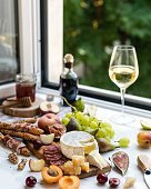istock Wine glass with appetizer, camembert, parmesan cheese and fruit variety 1158359205