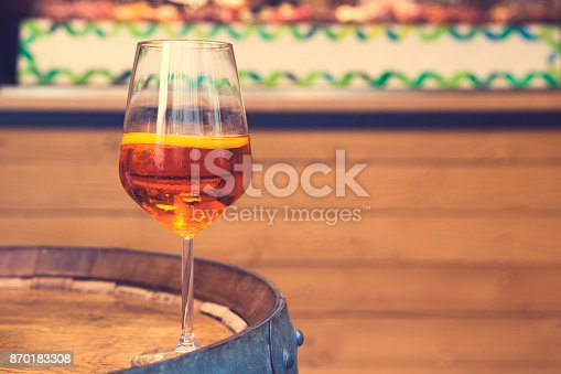 istock Wine glass with cocktail aperol spritz on the  original table in form of barrel 870183308