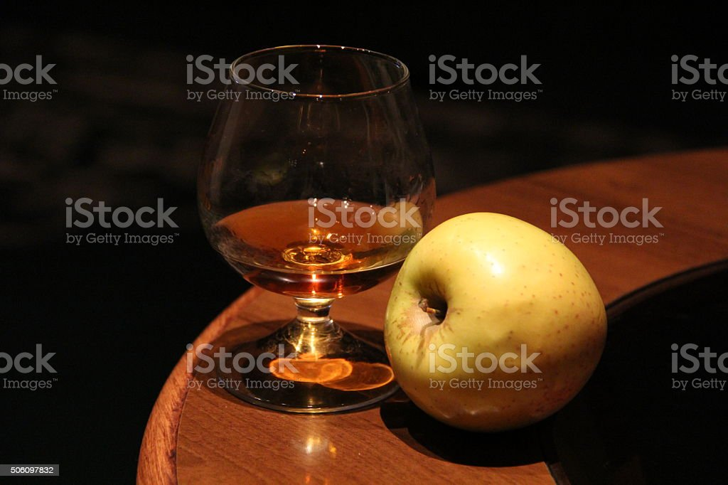 Wine glass with cognac and an apple stock photo