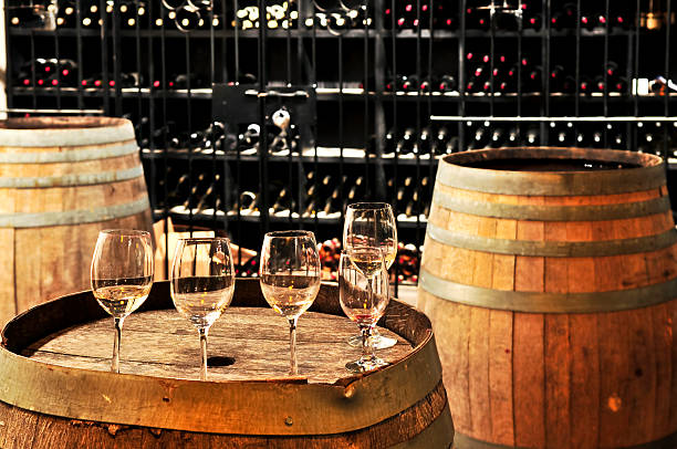 Wine  glasses and barrels Row of wine glasses on barrel in winery cellar cellar stock pictures, royalty-free photos & images